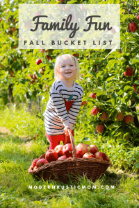 little girl apple picking in apple orchard with basket full of apples