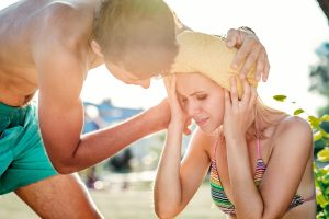 Young man helping woman in bathing suit with heatstroke, summer heat, sunny day